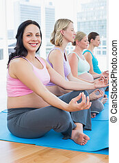 Content pregnant women meditating in yoga class with one smiling at camera in a fitness studio