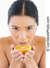 Content pretty woman holding orange in her hands