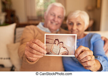 Content senior couple holding a photo of their youthful selves