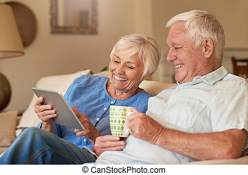 Content senior couple using a digital tablet on their sofa