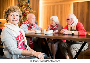 Content senior lady in cafe with friends