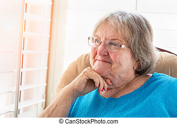 Content Senior Woman Gazing Out of Her Window