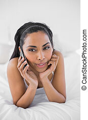 Content thinking woman phoning with smartphone