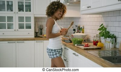 Content woman cooking ad dancing - Wonderful young model in...