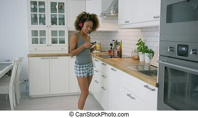 Content woman dancing with smartphone