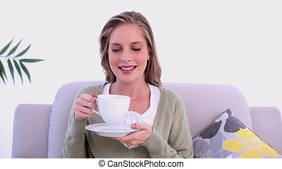 Content woman drinking from cup sitting on couch in bright living room