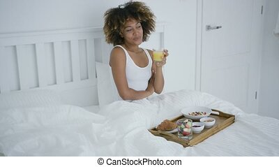 Content woman enjoying breakfast in bed - Young woman...