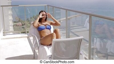 Content woman enjoying sunlight on terrace - Young fit girl...