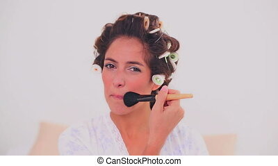 Content woman in hair curlers apply - Content brunette woman...