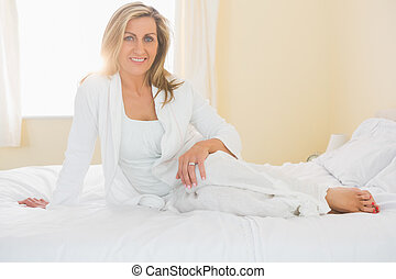 Content woman looking at camera posing on her bed