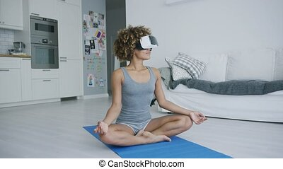 Sportive young woman sitting on blue mat at home relaxing and meditating in glasses of virtual reality looking content.