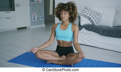 Content woman meditating on mat - Fit ethnic woman in...