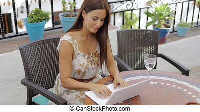Content woman on vacation with laptop - Young brunette in...