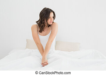 Content woman sitting and looking away in bed