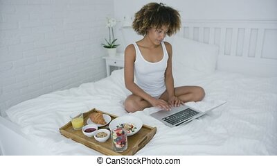 Content woman with laptop and breakfast - Young wonderful...