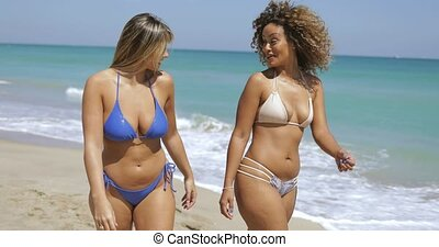 Content women strolling on beach