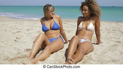 Content women sunbathing on sand - Two multiethnic women in...