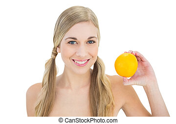 Content young blonde woman holding an orange