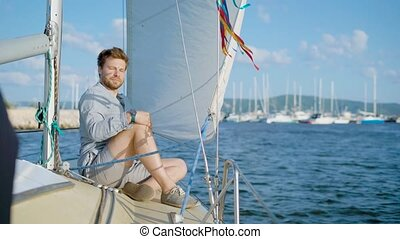 Content young man sitting on yacht and smiling at camera -...
