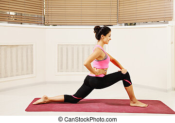 Contented brunette at stretching yoga pose
