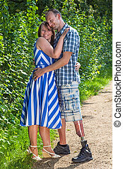 Contented loving couple with a handsome smiling handicapped...