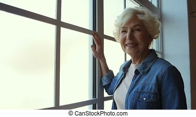 Contented pleasant senior woman standing near window - Nice...