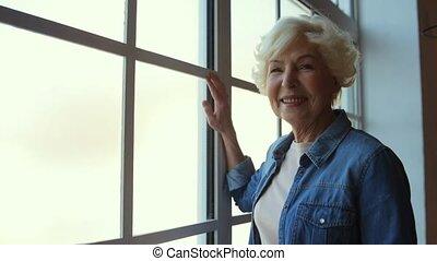 Contented pleasant senior woman standing near window - Nice...
