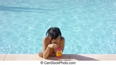 Contented woman at pool edge with drink - Contented...