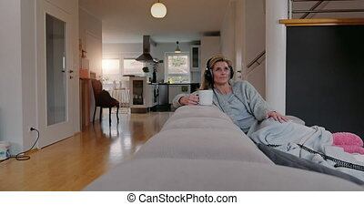 Contented woman listening to music at home