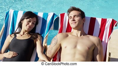 Contented young couple smiling as they sunbathe in deck...