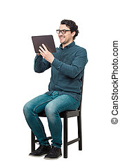Contented young male student, seated on a chair, using a PC tablet for entertaining. Modern education concept, working and studying from home. Happy man wearing eyeglasses looking at computer screen.