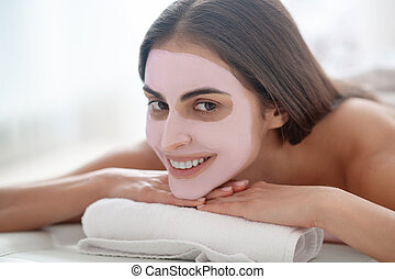 Young pretty woman with mask on her face smiling