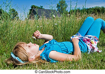 Contentment - Little girl with earphones and daisy in field.