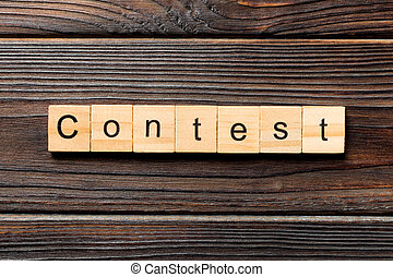 Contest word written on wood block. Contest text on wooden table for your desing, Top view concept