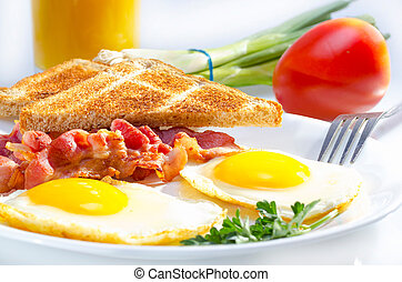Bacon with sunny side up eggs served with toasts.