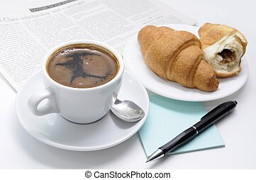 Cup of black coffee, croissants and breakfast accessories against a newspaper.