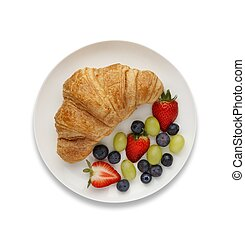Continental breakfast of a croissant and fruit, shot from above, on white with a drop shadow.
