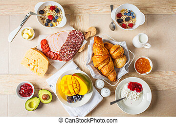Continental breakfast table with croissants, jam, ham, ...