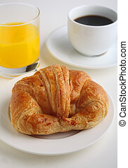 A Continental breakfast of croissant, orange juice and black coffee on a white background