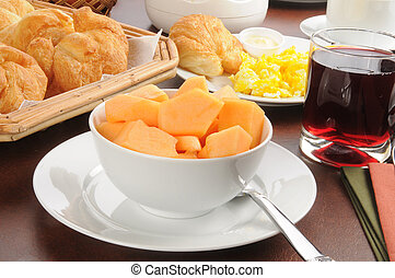 A continental breakfast with a bowl of cantaloupe and scrambled eggs