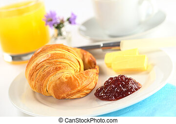 Continental breakfast with croissant, strawberry jam, butter, orange juice and coffee (Selective Focus, Focus on the jam)