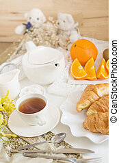 Continental breakfast with gold french croissants fruits and cup of tea on white table in a Morning light. Breakfast concept