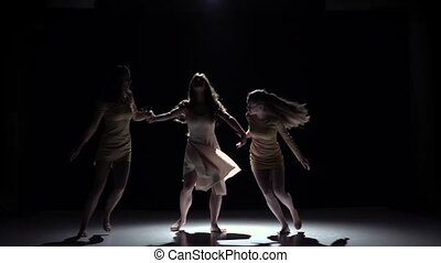 Continue contemporary dance of three girls in white dresses, on black, shadow, slow motion