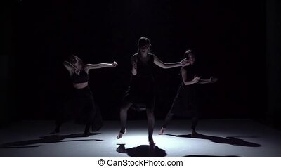 Continue graceful contemporary dance of three dancers in dark on black, shadow, slow motion