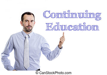 Continuing Education - Young businessman with small beard pointing up in blue shirt