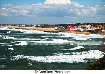 Permanent dark waves surge in Atlantic coast. The azure sky with a lot of white clouds is over Bay of Biscay. There are buildings and hotels of Biarritz in the background.