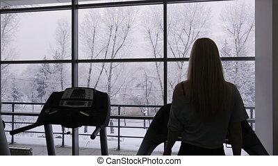 contour of the athlete sexy woman walking on a treadmill in the gym in front of panoramic windows with views of the snowy forest