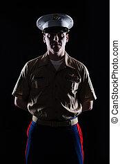Contour shot of US marine in blue dress uniform on black...