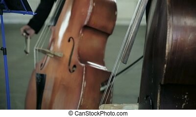 Contrabass fiddlestick strings play music stand. Close-up