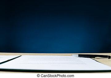 Contract in folder an a pen lying on office desk